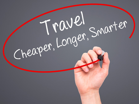 cheaper: Man Hand writing Travel Cheaper Longer Smarter  with black marker on visual screen. Isolated on grey. Business, technology, internet concept. Stock Photo
