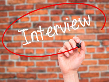 new recruit: Man Hand writing Interview with black marker on visual screen. Isolated on bricks. Business, technology, internet concept. Stock Photo
