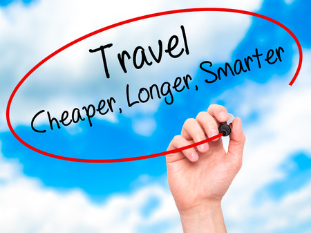cheaper: Man Hand writing Travel Cheaper Longer Smarter  with black marker on visual screen. Isolated on sky. Business, technology, internet concept. Stock Photo