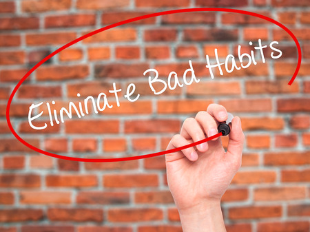 eliminate: Man Hand writing Eliminate Bad Habits with black marker on visual screen. Isolated on bricks. Business, technology, internet concept. Stock Photo