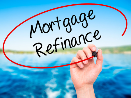 refinance: Man Hand writing Mortgage Refinance with black marker on visual screen. Isolated on nature. Business, technology, internet concept. Stock Photo