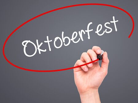 prost: Man Hand writing Oktoberfest with black marker on visual screen. Isolated on grey. Business, technology, internet concept. Stock Photo