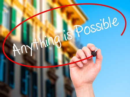 Man Hand writing Anything is Possible with black marker on visual screen. Isolated on city. Business, technology, internet concept. Stock Photo Stock Photo