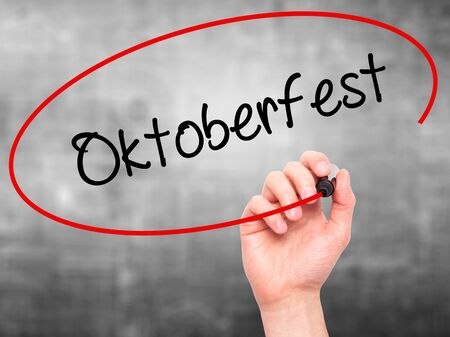 Man Hand writing Oktoberfest with black marker on visual screen. Isolated on grey. Business, technology, internet concept. Stock Photo