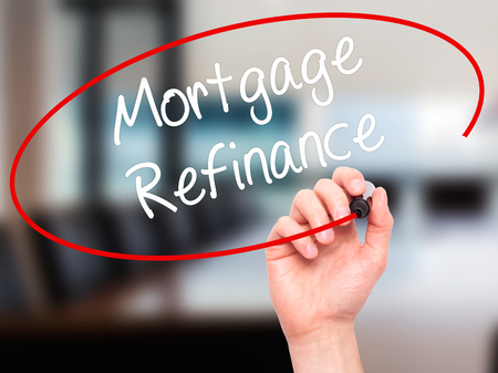 Man Hand writing Mortgage Refinance with black marker on visual screen. Isolated on office. Business, technology, internet concept. Stock Photo Stock Photo