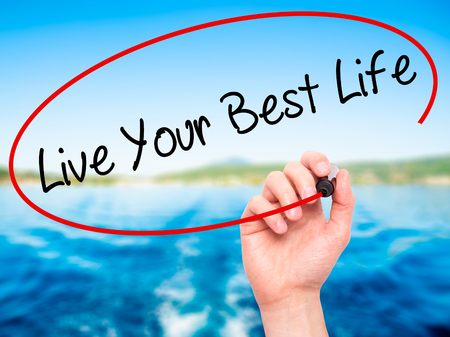 motivator: Man Hand writing Live Your Best Life with black marker on visual screen. Isolated on nature. Business, technology, internet concept. Stock Photo
