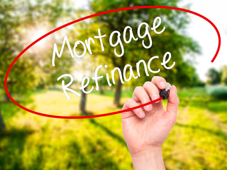 loaning: Man Hand writing Mortgage Refinance with black marker on visual screen. Isolated on nature. Business, technology, internet concept. Stock Photo