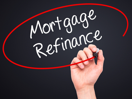 refinance: Man Hand writing Mortgage Refinance with black marker on visual screen. Isolated on black. Business, technology, internet concept. Stock Photo