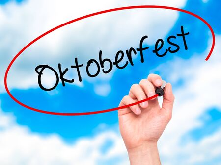 prost: Man Hand writing Oktoberfest with black marker on visual screen. Isolated on sky. Business, technology, internet concept. Stock Photo