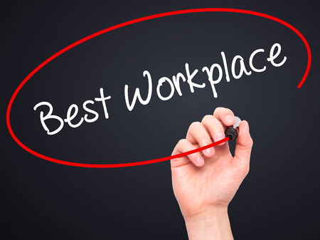 fulfilled: Man Hand writing Best Workplace with black marker on visual screen. Isolated on black. Business, technology, internet concept. Stock Photo