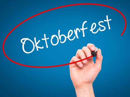 bier festival: Man Hand writing Oktoberfest with black marker on visual screen. Isolated on blue. Business, technology, internet concept. Stock Photo