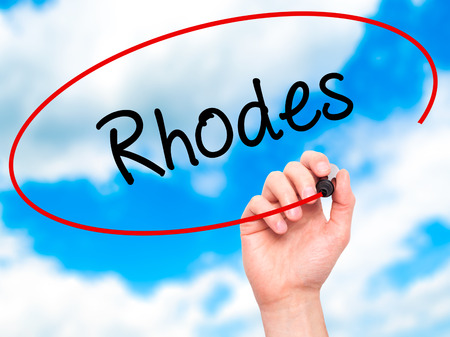 tsambika: Man Hand writing Rhodes with black marker on visual screen. Isolated on sky. Business, technology, internet concept. Stock Photo
