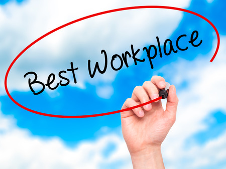 fulfilled: Man Hand writing Best Workplace with black marker on visual screen. Isolated on sky. Business, technology, internet concept. Stock Photo