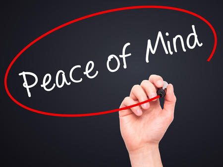 sense of security: Man Hand writing Peace of Mind black marker on visual screen. Isolated on black. Business, technology, internet concept. Stock Image