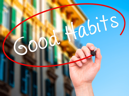 good habits: Man Hand writing Good Habits with black marker on visual screen. Isolated on city. Life, technology, internet concept. Stock Image Stock Photo