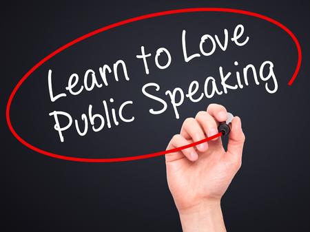 Escritura de la mano del hombre aprenda a amar a hablar en público con marcador negro en la pantalla visual. Aislado en negro. Negocios, la tecnología, el concepto de internet. imagen de archivo Foto de archivo - 52109489