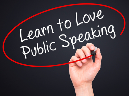 Man Hand writing Learn to Love Public Speaking with black marker on visual screen. Isolated on black. Business, technology, internet concept. Stock Image Stock Photo