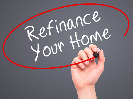 refinancing interest rates: Man Hand writing Refinance Your Home with black marker on visual screen. Isolated on grey. Business, technology, internet concept. Stock Image