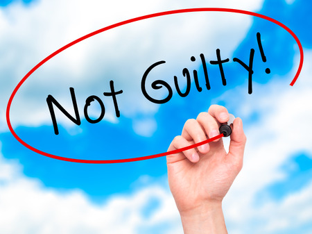 white backing: Man Hand writing NOT GUILTY with black marker on visual screen. Isolated on sky. Business, technology, internet concept. Stock Image