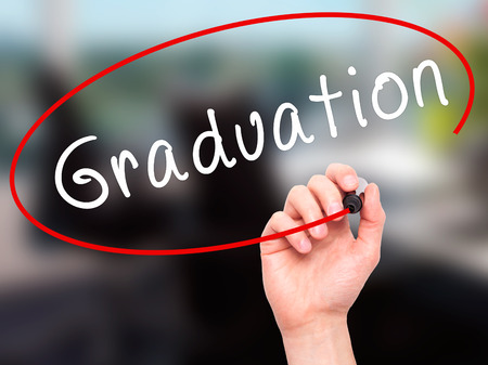 general knowledge: Man Hand writing Graduation with black marker on visual screen. Isolated on office. Business, technology, internet concept. Stock Image