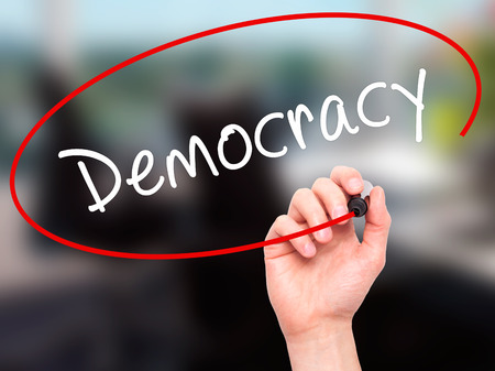 Man Hand writing Democracy with black marker on visual screen. Isolated on office. Business, technology, internet concept. Stock Image