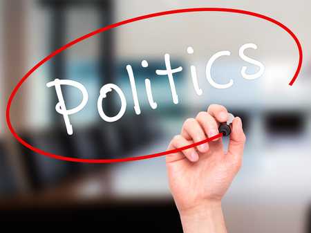 Man Hand writing Politics with black marker on visual screen. Isolated on office. Business, technology, internet concept. Stock Image Imagens