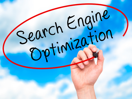 indexing: Man Hand writing Search Engine Optimization with black marker on visual screen. Isolated on sky. Business, technology, internet concept. Stock Image Stock Photo