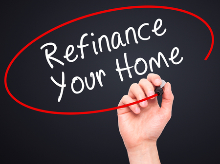 refinance: Man Hand writing Refinance Your Home with black marker on visual screen. Isolated on black. Business, technology, internet concept. Stock Image
