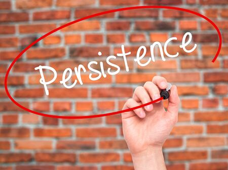 persist: Man Hand writing Persistence  with black marker on visual screen. Isolated on bricks. Business, technology, internet concept. Stock Photo Stock Photo