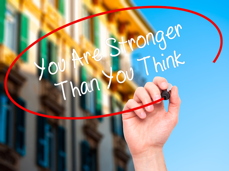 stronger: Man Hand writing You Are Stronger Than You Think with black marker on visual screen. Isolated on city. Business, technology, internet concept. Stock Photo Stock Photo