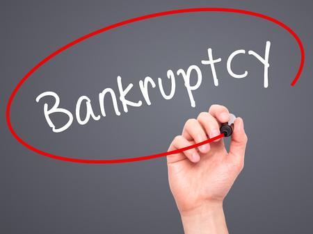 creditors: Man Hand writing Bankruptcy with black marker on visual screen. Isolated on grey. Business, technology, internet concept. Stock Image Stock Photo