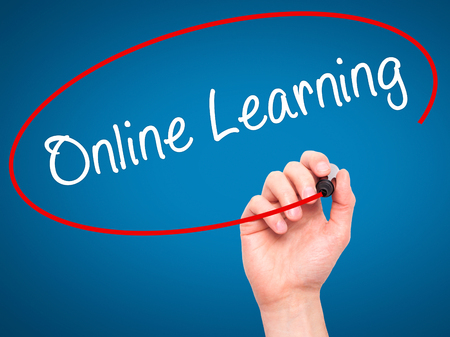 elearn: Man Hand writing Online Learning with black marker on visual screen. Isolated on blue. Business, technology, internet concept. Stock Image