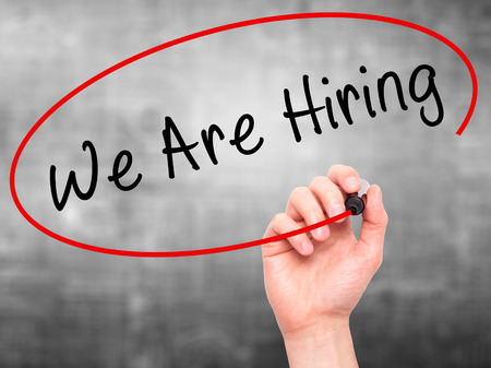 hiring: Man Hand writing We Are Hiring  with black marker on visual screen. Isolated on grey. Business, technology, internet concept. Stock Image Stock Photo