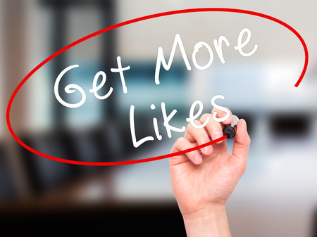 likes: Man Hand writing Get More Likes black marker on visual screen. Isolated on office. Business, technology, internet concept. Stock Image Stock Photo