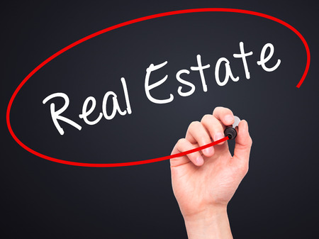 finer: Man Hand writing Real Estate  with black marker on visual screen. Isolated on black. Business, technology, internet concept. Stock Photo