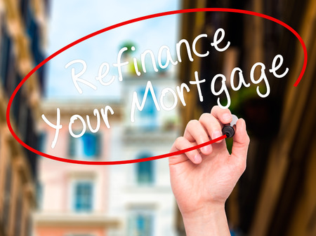 refinancing interest rates: Man Hand writing Refinance Your Mortgage with black marker on visual screen. Isolated on city. Business, technology, internet concept. Stock Image