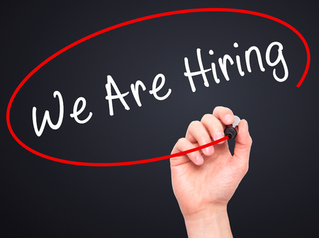 recruit help: Man Hand writing We Are Hiring  with black marker on visual screen. Isolated on black. Business, technology, internet concept. Stock Image