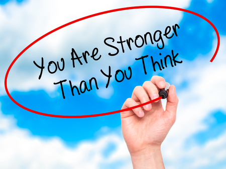 stronger: Man Hand writing You Are Stronger Than You Think with black marker on visual screen. Isolated on sky. Business, technology, internet concept. Stock Photo Stock Photo