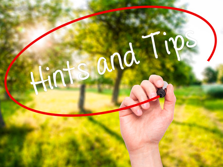 hints: Man Hand writing Hints and Tips with black marker on visual screen. Isolated on nature. Business, technology, internet concept. Stock Photo