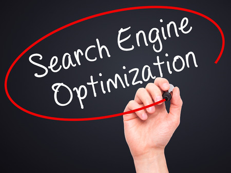 indexing: Man Hand writing Search Engine Optimization with black marker on visual screen. Isolated on black. Business, technology, internet concept. Stock Image