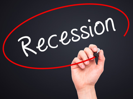 unemployment rate: Man Hand writing Recession with black marker on visual screen. Isolated on black. Business, technology, internet concept. Stock Image