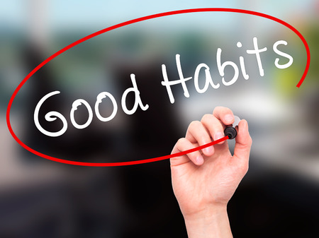 good habits: Man Hand writing Good Habits with black marker on visual screen. Isolated on office. Life, technology, internet concept. Stock Image