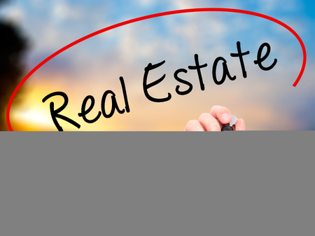 finer: Man Hand writing Real Estate  with black marker on visual screen. Isolated on nature. Business, technology, internet concept. Stock Photo