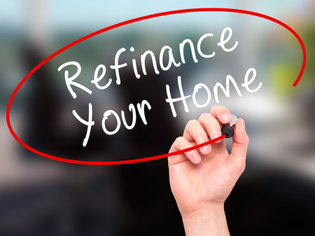 loaning: Man Hand writing Refinance Your Home with black marker on visual screen. Isolated on office. Business, technology, internet concept. Stock Image