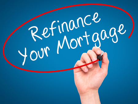 refinance: Man Hand writing Refinance Your Mortgage with black marker on visual screen. Isolated on blue. Business, technology, internet concept. Stock Image