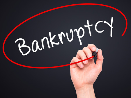 creditors: Man Hand writing Bankruptcy with black marker on visual screen. Isolated on black. Business, technology, internet concept. Stock Image