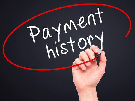 creditworthiness: Man Hand writing Payment history with black marker on visual screen. Isolated on black. Business, technology, internet concept. Stock Image