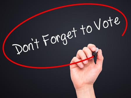 Escritura de la mano del hombre No se olvide de votar con marcador negro en la pantalla visual. Aislado en negro Negocios, tecnología, concepto de internet. Foto de stock