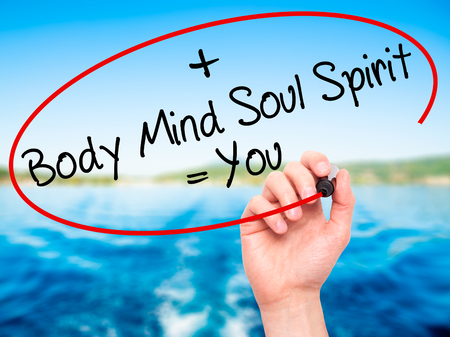 Man Hand writing Body + Mind + Soul + Spirit = You with black marker on visual screen. Isolated on nature. Life, technology, internet concept. Stock Image Standard-Bild
