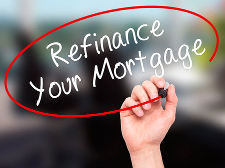 refinancing interest rates: Man Hand writing Refinance Your Mortgage with black marker on visual screen. Isolated on office. Business, technology, internet concept. Stock Image